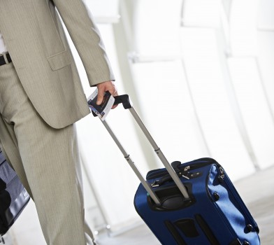man walking through airport with suitcase