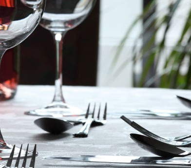 table setting with wine glasses and utensils