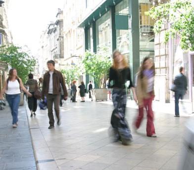 crowd walks outside in shopping area